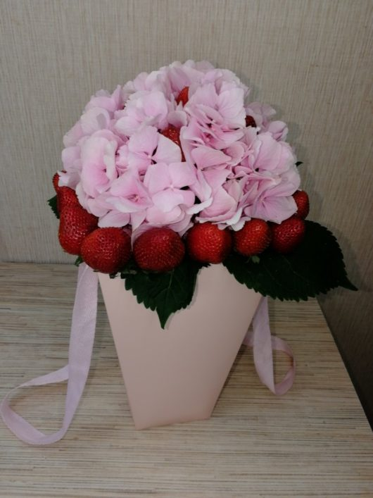 Композиция из розовой гортензии и клубники в картонном кашпо с ручками